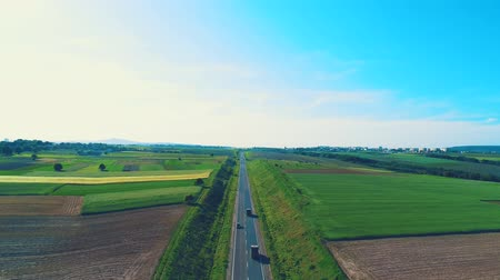 Aerial view, which slowly lowers its focus on a vast of trucks on a cinematic road, located in amazing landscape. 4K.