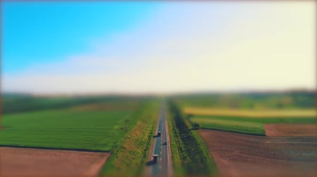 Aerial blurred view of different type cars driving along the empty gravel road through green meadows and agriculture fields landscape. 4K. Stock mozgókép