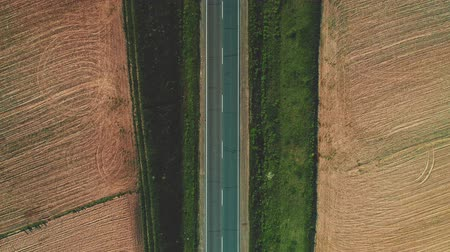 Aerial zoom out the road between fields. 4K.