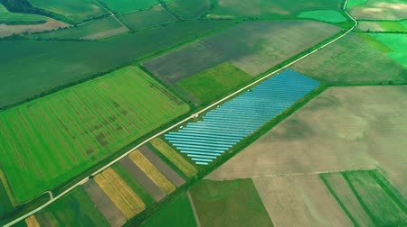 устойчивость : Aerial drone view of the large solar farm in the green fields. Zoom. 4K. Стоковые видеозаписи