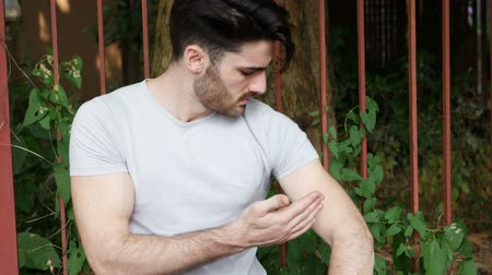 itchy : Handsome young man outdoor getting bitten by mosquito, and scratching his arm Stock Footage