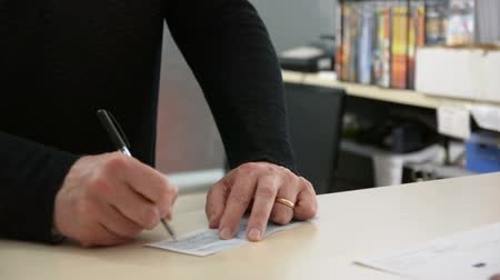 cheque : Male hand signing cheque and receiving document or contract from other persons hands, in office environment Stock Footage