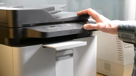 másológép : Male hand printing document on printer or fax or scanner, then retrieving paper sheet