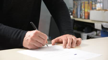 cheque : Male hand signing document and receiving check from other persons hands, in office environment