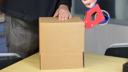 лента : Male hands packing small cardboard box with self-adhesive duct tape in office or warehouse