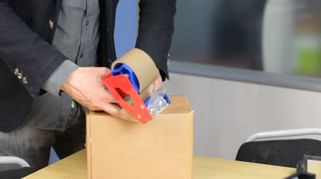 caixa de ferramentas : Male hands packing small cardboard box with self-adhesive duct tape in office or warehouse