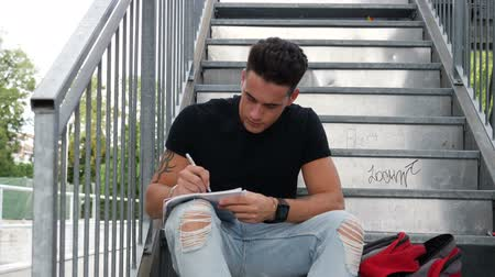 ручки : Young attractive man sitting on metal stairs, writing notes or letter on paper sheet with a pen