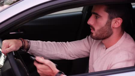 distraído : Inattentive Handsome Young Man Busy with his Mobile Phone While Driving a Car.