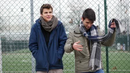 cimborák : Two handsome casual trendy young men, 2 friends, in an urban park chatting together Stock mozgókép