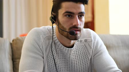mmorpg : Young handsome man playing video game and talking with online players through headset, while sitting on couch at home at night Stock Footage