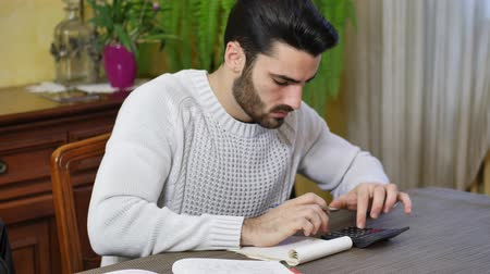 banknoty : Handsome young man using calculator and accounting at table at home in his living room