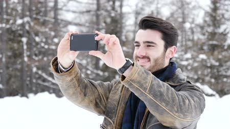 pic : Handsome young man using smarpthone to take photographs of the landscape, while posing among snowy woods in the mountain Stock Footage