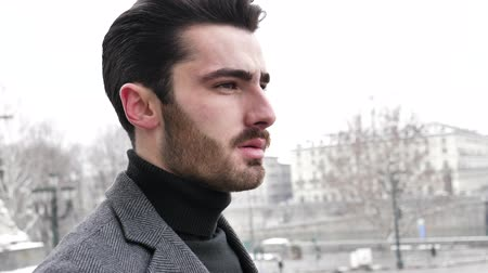 országúti : Handsome young man walking outside during winter, in snowy Turin, Italy, in urban setting Stock mozgókép