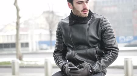 couro : Handsome trendy man wearing black leather jacket sitting and typing on cell phone, outdoor in city setting in winter day shot Vídeos