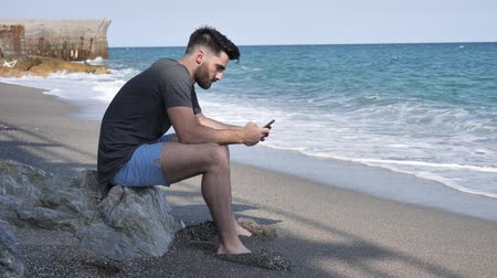 distraído : Shirtless Young Handsome Man Busy with his Mobile Phone While Sitting at the Beach Boulders