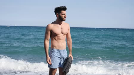 üstsüz : Handsome young man sitting on a beach, feeling lonely and sad or simply relaxed, shirtless wearing boxer shorts Stok Video
