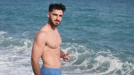 munch : Young athletic confident man biting chocolate or protein bar on background of sea or ocean in summer