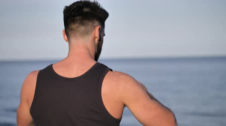 perfil : Young handsome man at the seaside using smartphone to take shots and film footage of the sea or ocean