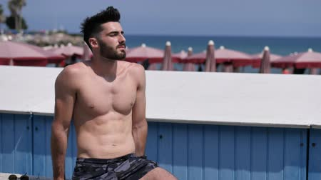 üstsüz : Attractive muscular young man soaking in the sun on seaside boardwalk or seafront, showing muscles on chest, abs, arms Stok Video