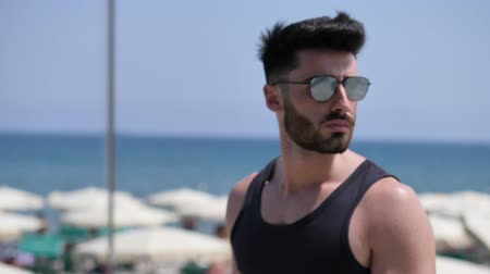tank top : Side view of attractive fit athletic young man soaking in the sun on seaside boardwalk or seafront, wearing black tank-top