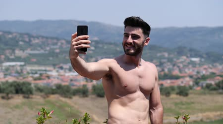 üstsüz : Young handsome man using smartphone to take selfie photo while standing shirtless on a balcony at the seaside over countryside landscape