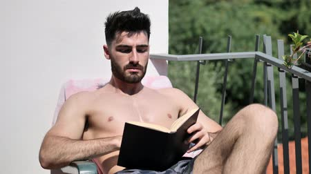üstsüz : Shirtless Young Man Drying Off in Hot Sun Reading a Book, Muscular Man Wearing Bathing Suit Sunbathing on Beach Lounge Chair