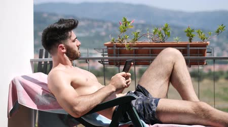 üstsüz : Shirtless Young Man Drying Off in Hot Sun Reading an Ebook with Electronic Reader, Muscular Man Wearing Bathing Suit Sunbathing on Beach Lounge Chair