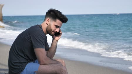 mobilitás : Athletic man at the seaside using cell phone to call someone with the sea behind him, sitting on a rock