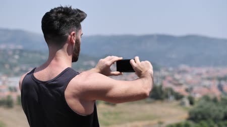 tank top : Young handsome man using smartphone to take shots and film footage of the landscape at the seaside