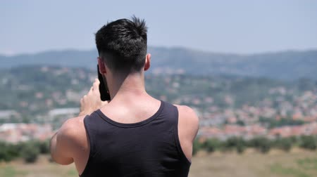 tank top : Young handsome man using smartphone to take shots and photos of the landscape at the seaside