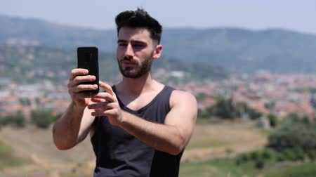 férfias : Young handsome man using smartphone, videocalling someone while standing on a balcony at the seaside over countryside landscape Stock mozgókép
