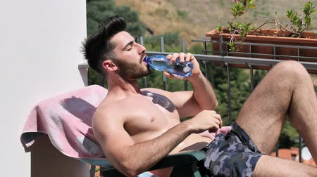üstsüz : Shirtless Young Man Drying Off in Hot Sun, Drinking Water from Plastic Bottle, Muscular Man Wearing Bathing Suit Sunbathing on Beach Lounge Chair Stok Video