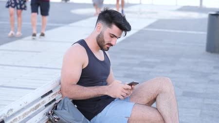 receber : Young handsome man using smartphone, typing text message to someone while sitting on a bench at the seaside over countryside landscape Stock Footage