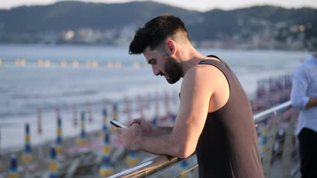 Athletic young man at the seaside using cell phone to type message while looking at the sea and beach