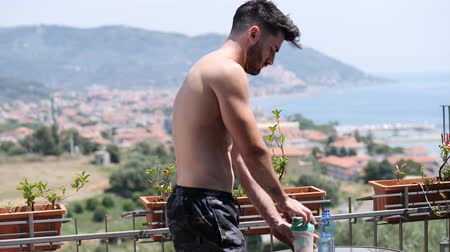 üstsüz : Young muscular shirtless man drinking protein shaker from blender on a balcony in summer
