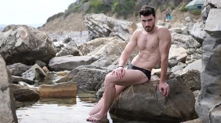 üstsüz : Handsome muscular young man sitting on a rocky beach, relaxed, shirtless