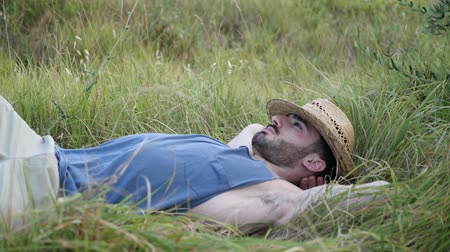 szieszta : Attractive, fit young man relaxing lying in a grass field, wearing straw hat