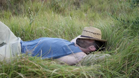 iyi seyir : Attractive, fit young man relaxing lying in a grass field, wearing straw hat