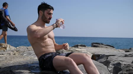 borrifar : Attractive shirtless muscleman on the beach pouring down water on his chest from plastic bottle Stock Footage