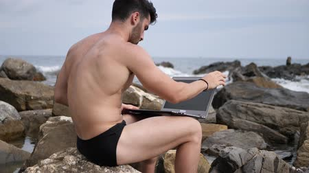 üstsüz : Young handsome man working on laptop computer, typing on keyboard while at the beach in front of the sea Stok Video