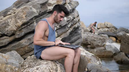 mężczyźni : Young handsome man working on laptop computer, typing on keyboard while at the beach in front of the sea Wideo