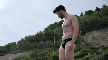 üstsüz : Attractive fit athletic young man soaking in the sun at rocky beach with woods behind him, shirtless Stok Video