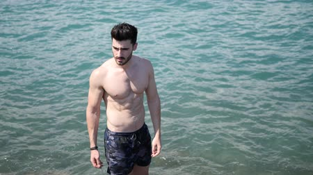 üstsüz : Handsome muscular young man standing in the sea by the coast and the beach