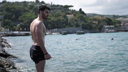 üstsüz : Handsome muscular young man standing at the beach then diving into the sea or ocean Stok Video