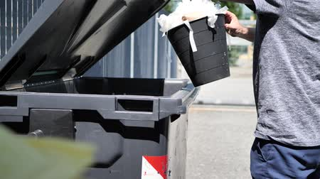 litter box : Hand of man throwing away mixed garbage in big waste container for recycling