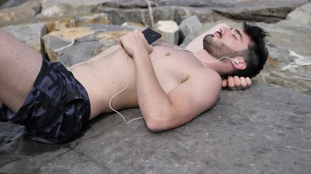 repousante : Solitary fit young man laying on a stone at the beach while listening to music through earphones