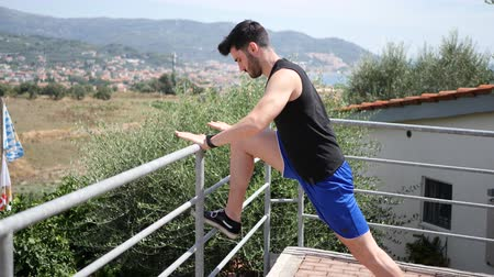 esneme : Athletic attractive young man exercising and stretching outdoor on terrace in summer day