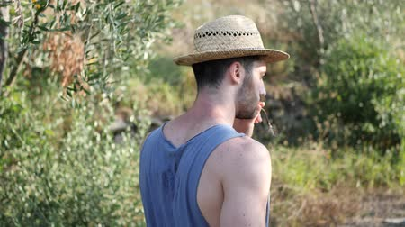 szieszta : Attractive, fit young man relaxing walking in a grass field, wearing straw hat Stock mozgókép