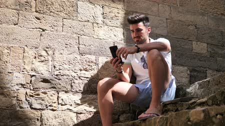 Лигурия : Young male tourist exploring old italian town of Cervo in Liguria region, using cell phone