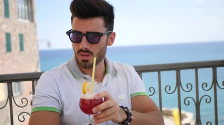аперитив : Young handsome man drinking a cocktail, on terrace outdoor at bar in summer over the sea Стоковые видеозаписи
